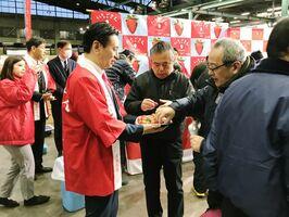 赤い法被を着て、市場関係者に「いちごさん」を売り込む佐賀県の山口知事=東京・大田区の大田市場