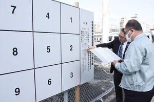 佐賀県議選のポスター掲示板の記載に間違いがないか、確認をする佐賀市選管職員=駅前中央1丁目