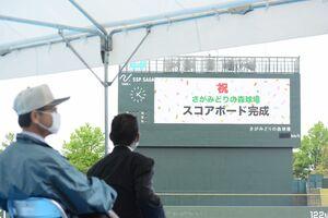 完成したスコアボードと球場に駆け付けた野球関係者たち=佐賀市のさがみどりの森球場