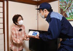 岩瀬恵美子さん(左)に戸別受信機を手渡す小松政市長=武雄市朝日町の岩瀬さん宅