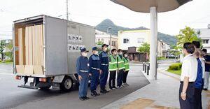 人吉市に届ける段ボール間仕切りを積んだトラックと運搬に当たる職員=武雄市役所