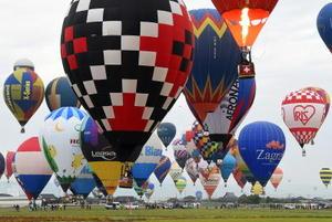 熱気球世界選手権の競技初日。マーカーを投下するターゲット上空にバルーンを近づけようと、競い合うパイロット=31日朝、小城市芦刈町
