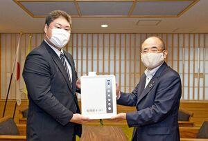 秀島敏行市長に除菌電解水給水器を手渡す永池の永池明裕社長(左)=佐賀市役所