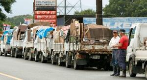 災害ごみ置き場の前にできたトラックの列=11日午前8時19分、熊本県人吉市