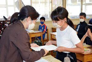 担任の先生から通知表を受け取る児童=有田町の曲川小