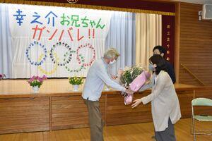 ストリゼウスキー・リチャード園長(左)から花束を受け取る柳本幸之介選手の両親=伊万里市二里町のカトリック幼稚園