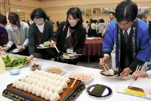 初摘みノリの試食会で、手巻き寿司やおにぎりを作る来場者=佐賀市のマリトピア