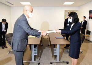 九州電力の豊嶋直幸取締役常務執行役員(左)へ回答書を手渡す小林万里子副知事=1日午後、県庁
