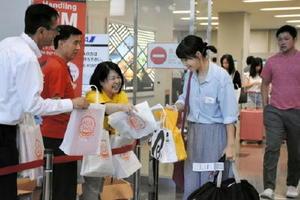 チラシやイベントグッズが入ったバッグを受け取る帰省客ら=佐賀市の九州佐賀国際空港