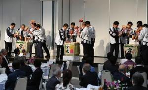 一斉に鏡開きする参加者たち=西松浦郡有田町の炎の博記念堂