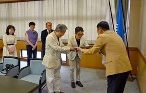 峰市長(右端)から感謝状を受け取る河内野信恒さん、江頭紘一さん=唐津市役所