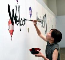 「ロマンシング佐賀3」イラスト展の特設ブースに執筆する江島さん=県立美術館