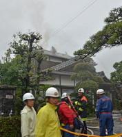 民家の屋根に登り、消火活動をする消防署員ら。落雷が原因で出火したとみられている=6日午前6時ごろ、鳥栖市山浦町