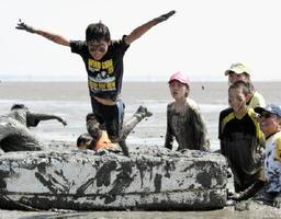 浮島を飛びながらゴールを目指す「ジャン・ピン・グゥ」でゴール地点に到着し、そのまま潟に飛び込む児童=鹿島市の七浦海浜スポーツ公園