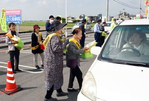 安全運転などを呼び掛けながらチラシを配る参加者=みやき町の県道北茂安三田川線沿い
