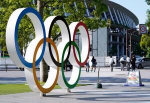 国立競技場(奥)と五輪マークのモニュメント=6月、東京都新宿区