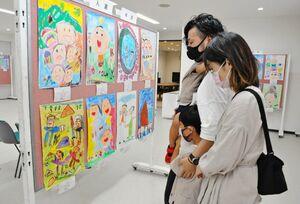 じっくりと作品を眺める家族=佐賀市のミサワホーム佐賀