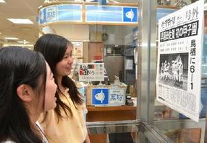 早稲田佐賀の初優勝を伝える号外に見入る高校生=佐賀市のJR佐賀駅