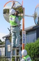 スポンジを使ってミラーを磨き上げ、角度を調整した神埼建設業協会の会員=神埼市北部
