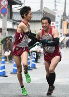 鬼塚体協の上野将信選手(左)がトップで山﨑久光選手へたすきリレー=6-7区中継所