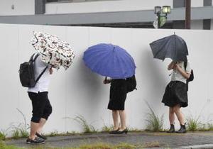台風の影響による強風で傘を押さえて通勤する人の姿も目についた=5日午前7時43分、佐賀市松原