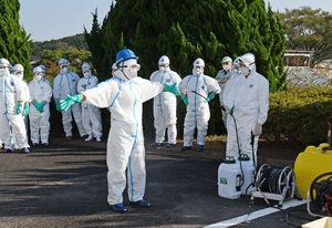 防疫の実地演習で、防護服を全身消毒して除染する参加者=唐津市鎮西町
