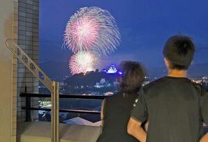 打ち上げられる花火を自宅から堪能する親子=唐津市西城内