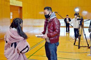 撮影の合間に出演者と話す江口監督(中央)=唐津市鎮西町の波戸岬少年自然