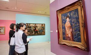 岡田三郎助と女性画家の作品に見入る来場者=佐賀市の県立図書館