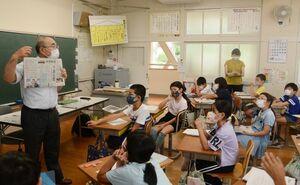 多久島文樹デスク(左)から新聞の作り方を学ぶ子どもたち=嬉野市塩田町の塩田小