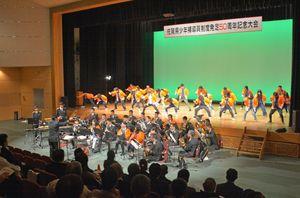 少年補導員制度発足50周年を記念してステージ上では県警音楽隊による演奏や大学生によるよさこいソーラン節のパフォーマンスが披露された=小城市三日月町の「ドゥイング三日月」