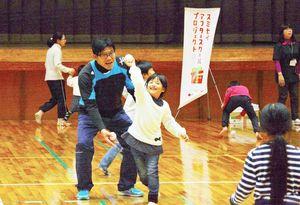 川崎憲次郎さんに教えてもらながらボールを投げる子ども=有田町文化体育館
