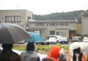 男が立てこもった運送会社「上田コールド」の本社と報道陣=15日午前7時39分、島根県出雲市