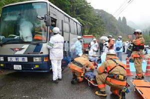 トンネル内で大型バスが事故を起こしたと想定し、訓練をする関係者=鹿島市山浦の奥平谷キャンプ場入り口