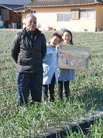 祖父松尾隆信さんのタマネギ畑で。左から、松尾さん、渡邊直穂さん、二葉さん=杵島郡白石町