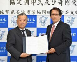 災害時物資協定書を手にする田島健一町長(左)と岡幹也支部長=白石町役場