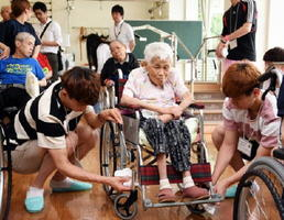 利用者が乗る車椅子を丁寧に磨く韓国の学生たち=鹿島市山浦の鹿島療育園