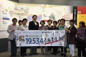 1万9534人目の来場者になった佐賀市の久野絹子さん(左から5人目)と佐賀市老人クラブ連合会のメンバー=佐賀市の県立博物館