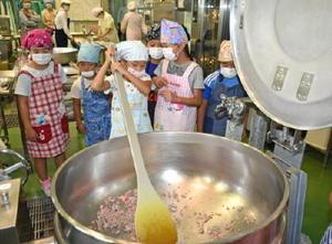 1㍍以上あるしゃもじを使ってミンチを炒める子どもたち=大町町の給食センター