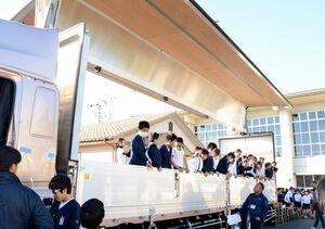 大型トラックの「ウイング車」の荷台に乗り込んだ児童たち=吉野ヶ里町の三田川小
