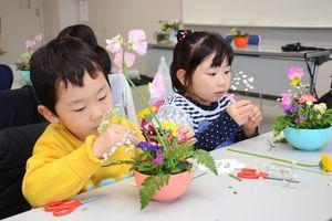 目の前のボウルに集中して花を生ける福富保育園の子どもたち=白石町の福富ゆうあい館