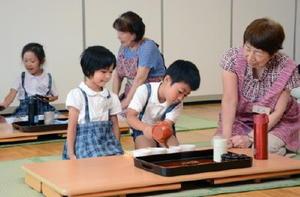 おもてなしの心を学ぶ煎茶教室で、お茶の濃さが一緒になるように回し注ぎを実践する園児たち=神埼市の神埼保育園