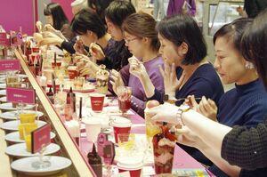 回転ずし風のレーンにのった果物やスポンジ生地などを組み合わせてパフェを作るイベント=24日、東京都渋谷区の高島屋新宿店