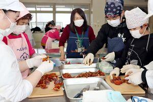 教わりながら巻き柿づくりに挑戦する学生ら=佐賀市の佐賀女子短期大学