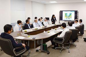 各研究機関の担当者から説明を聞く山口祥義知事(左)ら=県庁