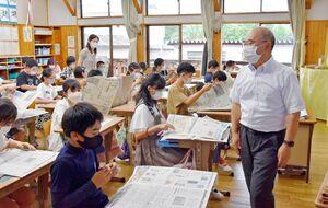 実際の佐賀新聞の紙面を使いながら見出しの付け方などを学ぶ児童=嬉野市の久間小学校
