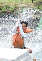 恐怖心を振り払い、水しぶきを上げてターザンに臨む参加者