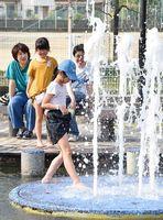 強い日差しの下、水遊びを楽しむ子どもたち=22日午後、小城市の小城公園