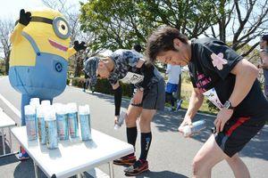「ミニオン」の着ぐるみ姿でランナーに冷却スプレーを勧めた川﨑哲也さん(左)=佐賀市の多布施川沿い