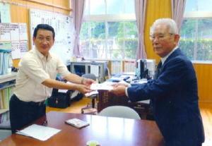 母校の西川登小の原口常博校長に寄贈するテントなどの目録を手渡す福田任さん(右)=武雄市の同校
